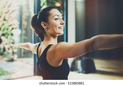 Portrait of gorgeous young woman practicing yoga indoor. Beautiful girl practice Warrior of Light asana.Calmness and relax, female happiness.Horizontal, blurred background