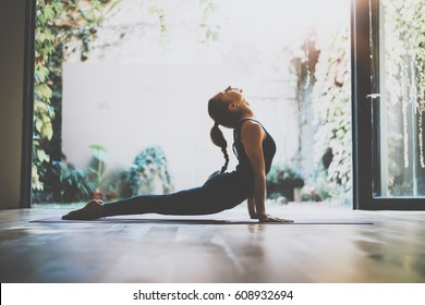 Portrait of gorgeous young woman practicing yoga indoor. Beautiful girl practice cobra asana in class.Calmness and relax, female happiness.Horizontal, blurred background.Visual effects