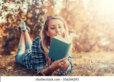 Portrait of a gorgeous young woman reading a book in the autumn park.