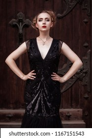 Portrait goth girl wearing black dress stands near red wood door .Beautiful outdoor, white skin red lips and blonde hair plaited .Halloween Vampire beautiful woman portrait