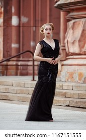 Portrait goth girl wearing black dress stands near red building .Beautiful witch outdoor, white skin red lips and blonde hair plaited .Halloween Vampire beautiful woman portrait