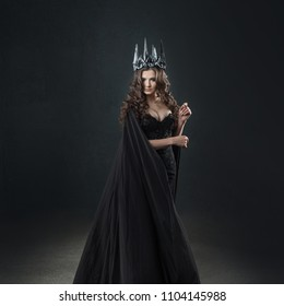 Portrait of a Gothic Princess. Beautiful young brunette woman in metal crown and black cloak. Mystical image