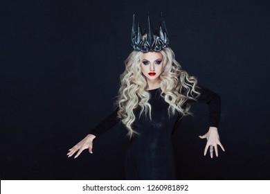 Portrait of a Gothic Princess. Beautiful young blonde woman in metal crown and black cloak. Mystical image