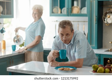 Portrait of grandad drinking tea at the dining table and looking with a slight grin. Old couple spending time together at the kitchen.