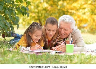 Portrait of grandchildren and grandfather doing homework in park