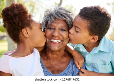 Portrait Of Grandchildren Kissing Grandmother In Park