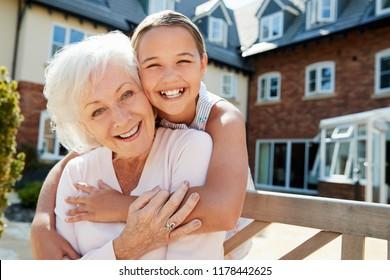 Portrait Of Granddaughter Hugging Grandmother On Bench During Visit To Retirement Home