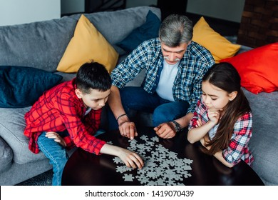 Portrait of grandfather and grandchild playing at home. Man and kid assembling Jigsaw Puzzle..