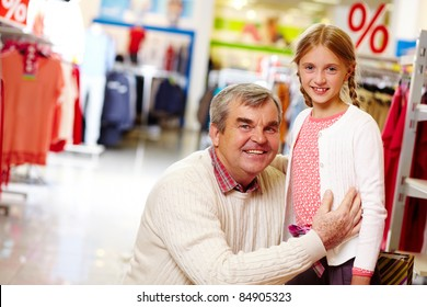 Portrait of grandfather and granddaughter in clothing department