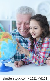 Portrait of grandfather and granddaughter exploring world globe