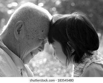 Portrait of grandfather and granddaughter, smiling at each other , BLACK AND WHITE , B&W