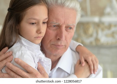 Portrait of grandfather and granddaughter thinking about something