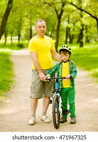Portrait of grandfather and grandson with a bicycle
