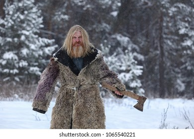 Portrait of grandfather with long hair and a beard in a sheepskin coat, with an ax in the winter forest