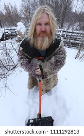 Portrait of grandfather with long hair and a beard in a sheepskin coat, with a shovel in the yard