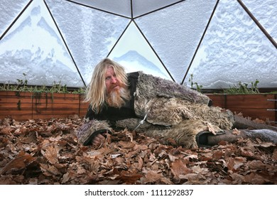 Portrait of grandfather with long hair and a beard in a sheepskin coat, in Dome greenhouse