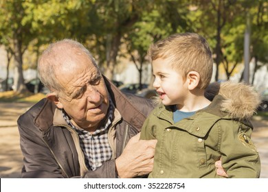 Portrait of a grandfather and son smiling in the park