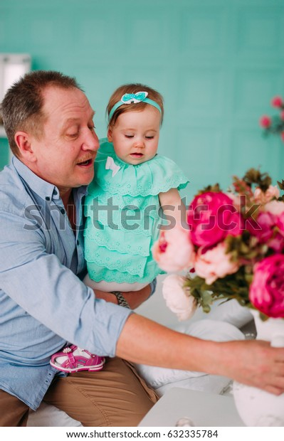 Portrait of a grandfather wearing blue  shirt with his small pretty granddaughter hugging him and listening attentively, studio shot