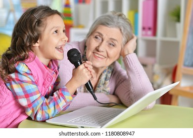 Portrait of grandmother and daughter singing karaoke
