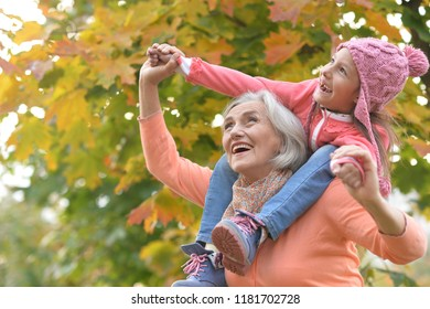 Portrait of grandmother and granddaughter in autumn park