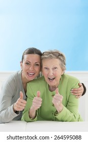 Portrait of grandmother and granddaughter showing thumbs up