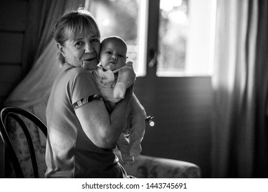 Portrait of grandmother and her grand daughter. Black and white image with selective focus, noise effect and toning.