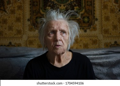 Portrait of grandmother at the home.  Grandmother is sitting on a sofa in her room. She just woke up.