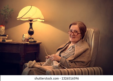 Portrait of a grandmother knitting in armchair. Image with selective focus and toning.