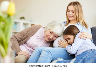 Portrait of grandmother and little girl listening to pregnant belly of smiling young woman, copy space