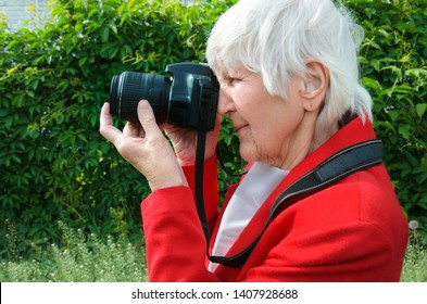 portrait of grandmother make photo outdoors at sun day. modern caucasian granny hold her camera. she using photocamera, adult hand of old lady. technology lifestyle