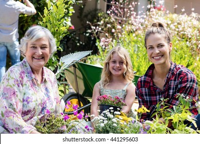Portrait of grandmother, mother and daughter gardening together in garden