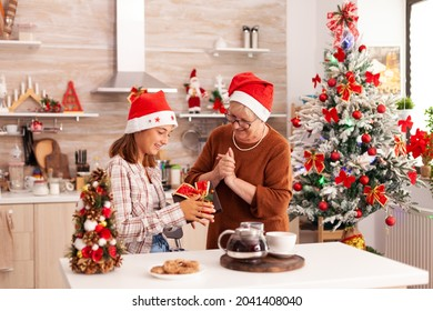 Portrait of grandmother surprising granddaughter with xmas wrapper present during christmastime in x-mas decorated kitchen celebrating christimas holiday. Family enjoying winter season together