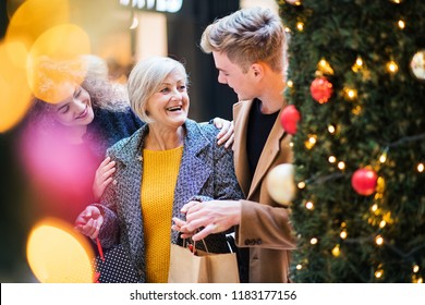 A portrait of grandmother and teenage grandchildren in shopping center at Christmas.