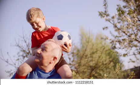 Portrait of grandpa with his grandson on the neck with soccer ball