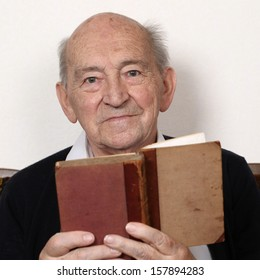 Portrait of a grandpa reading fairy tales from an old book
