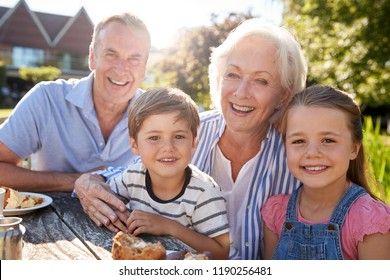 Portrait Of Grandparents With Grandchildren Enjoying Outdoor Summer Snack At Cafe
