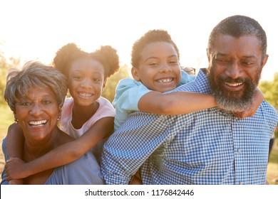 Portrait Of Grandparents With Grandchildren Enjoying Walk In Park Together