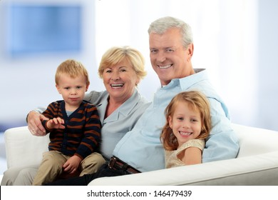 Portrait Of Grandparents With Grandchildren Relaxing Together On Sofa at Home