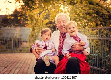 Portrait of grandparents with grandchildren in Ukrainian costume at sunset