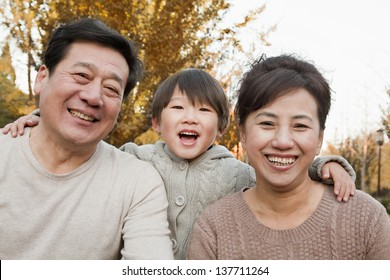 Portrait of Grandparents and Grandson in the Park