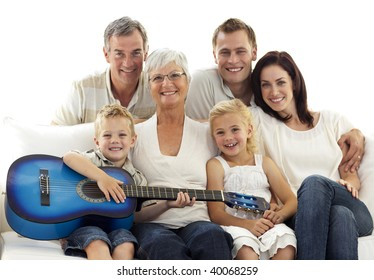Portrait of grandparents, parents and children playing guitar at home