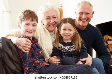 Portrait Of Grandparents Sitting On Sofa With Grandchildren