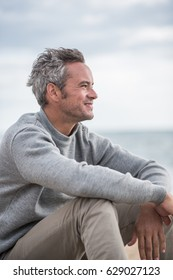 Portrait of a Gray haired man sitting on a rock at the beach. He wears a sweater