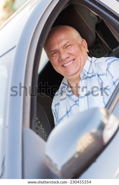 Portrait of  gray-haired man in  car.