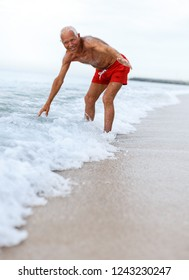 Portrait of great mature man checks the water temperature on the beach