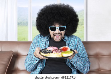Portrait of a greedy man with curly hair, sitting on the sofa while holding a plate of tasty donuts and wearing sunglasses