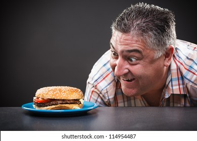 Portrait of a greedy man looking at burger on gray background
