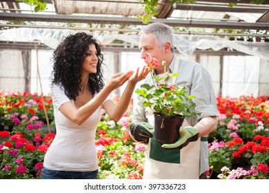 Portrait of a greenhouse worker giving a plant to a customer