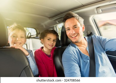 Portrait of a grey hair father with beard and his two kids in the car. The ten years old brother and sister are sitting in the back, they are wearing long sleeves shirts. The father have his seat belt