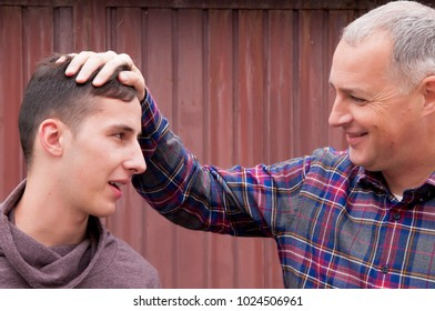 Portrait of grey haired father in plaid t-shirt and his handsome son